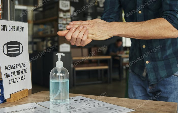 Man rubbing hands together using hand sanitiser in restaurant