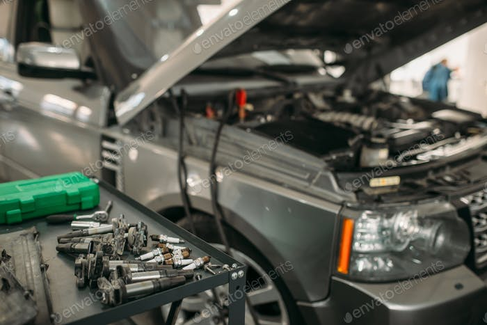Car with opened hood, battery recharging process
