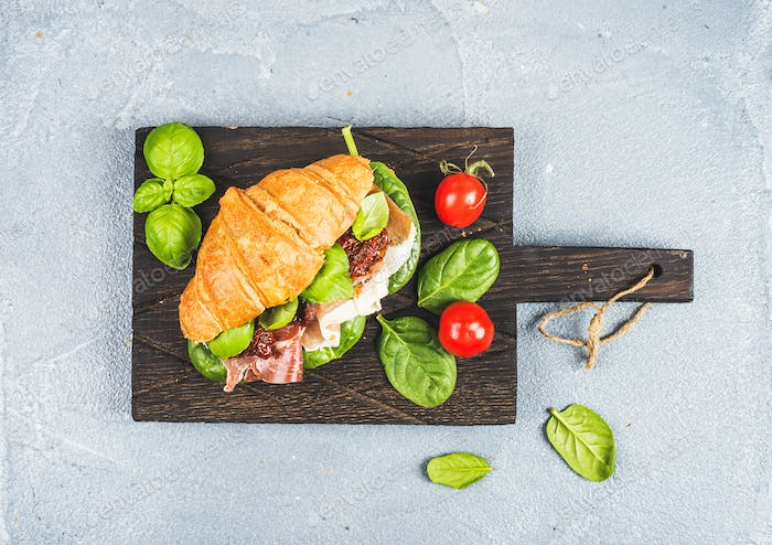 Croissant sandwich with smoked meat Prosciutto di Parma