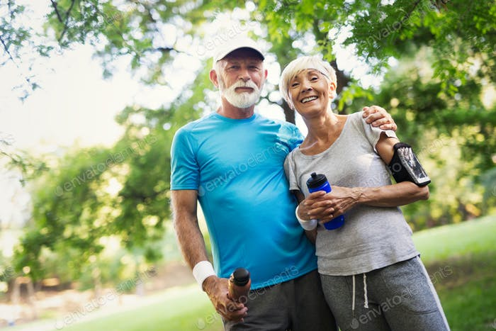 Fitness, sport and lifestyle concept - happy mature couple in sports clothes outdoors