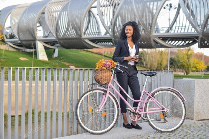 Business black woman standing by her vintage bicycle speaking on