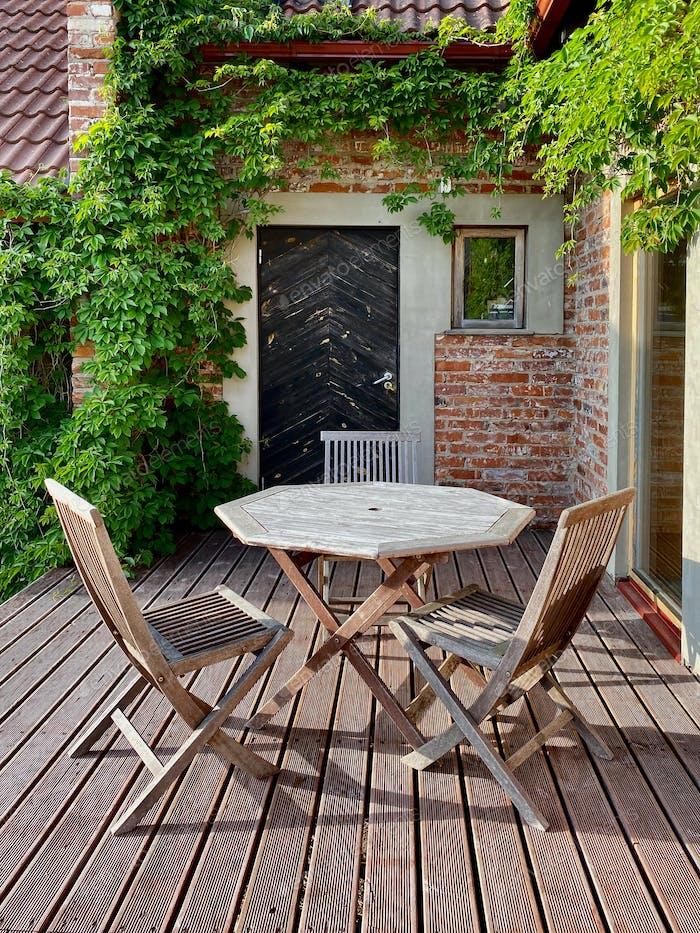 Terrasse mit Holztisch und Stühlen