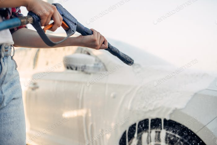 Female person wash off the foam from car