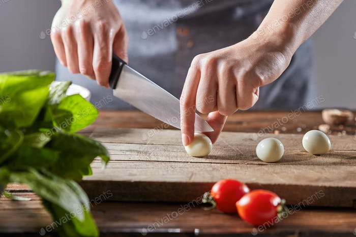 On a wooden table, the hands of a woman cut quail eggs on an old wooden board. Step by step salad