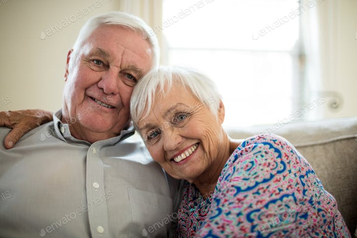 Portrait of happy senior couple embracing each other in living room