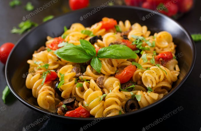 Pasta Fusilli  with tomatoes, beef and basil in black bowl on table.