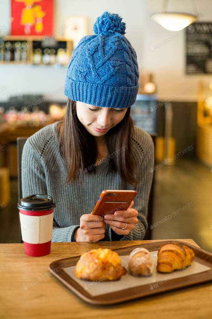 Young Woman use of smart phone in coffee shop at morning