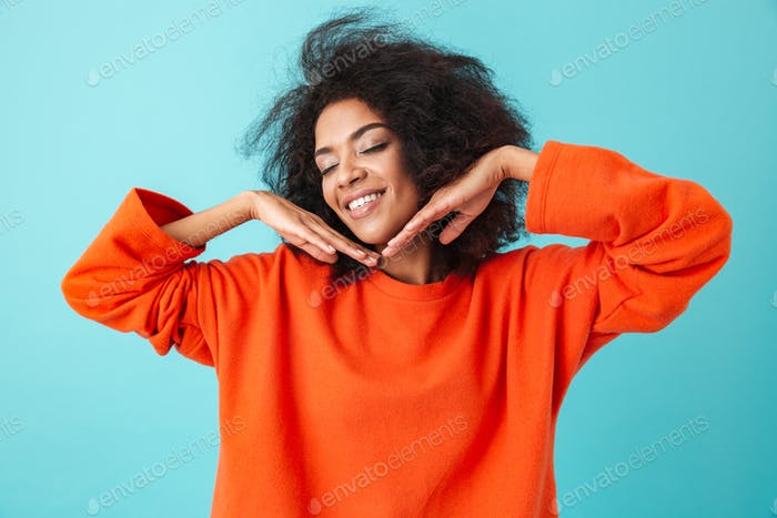 Young american woman in orange shirt posing on camera with lovel