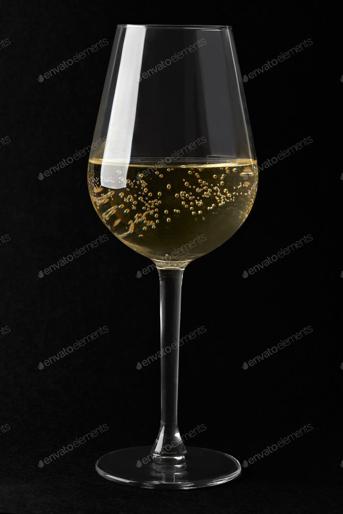 White sparkling wine glass on black background, clipping path in