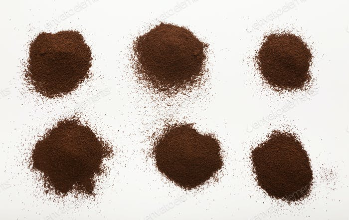 Heaps of brown ground coffee beans isolated on white