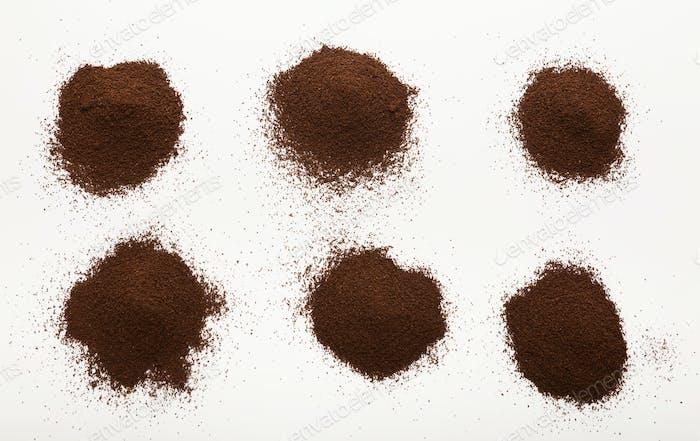 Haufen von braun gemahlenen Kaffeebohnen isoliert auf weiß