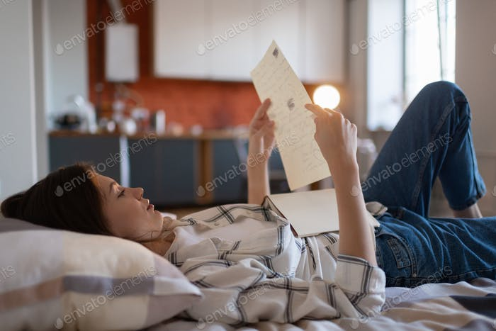 Girl reading notes for exam in bed