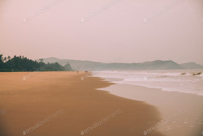 beautiful seashore with sandy beach and mountains in fog