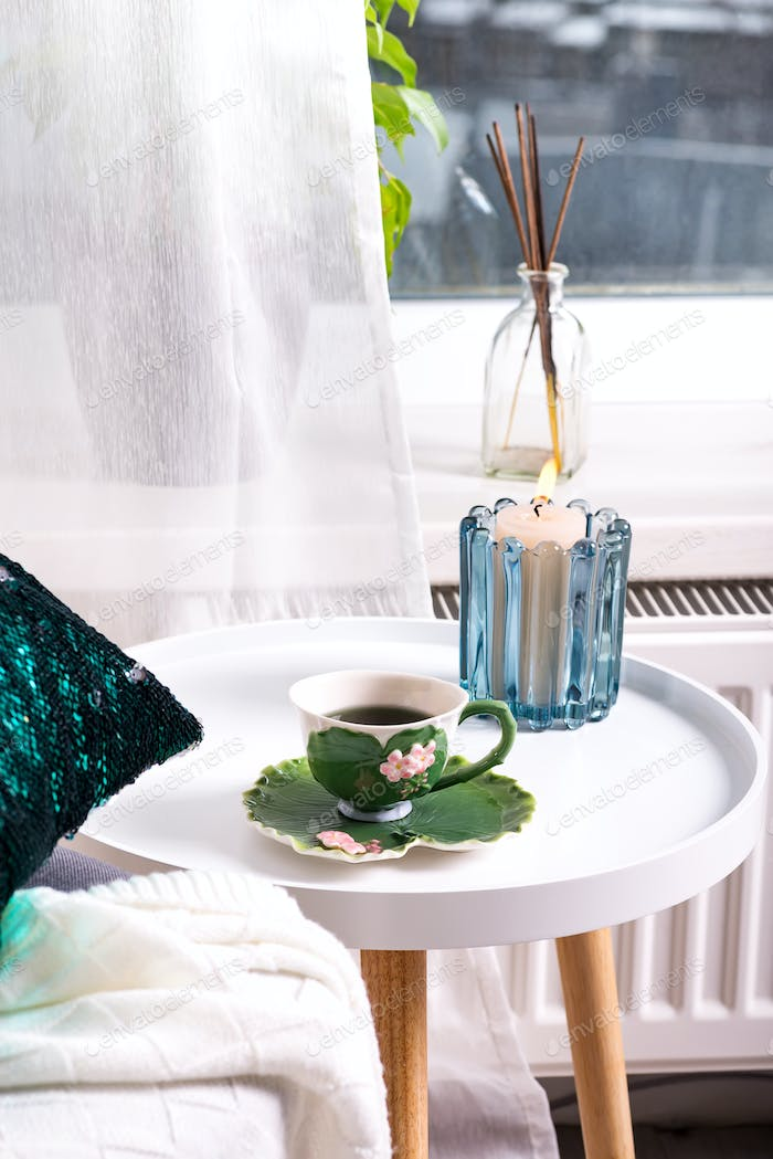 a cup of herbal tea on a table, a knitted wool blanket on a chair and candle over window . Bedroom