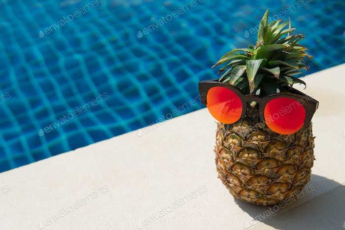 Funny Portrait Of Pineapple In Sunglasses On A Background Of A Swimming Pool.