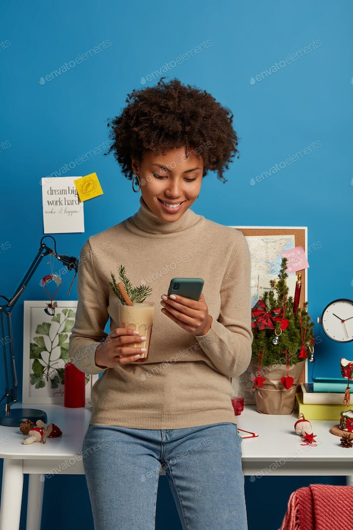 Cheerful young woman with Afro hair checks newsfeed on smartphone, satisfied to read followers messa