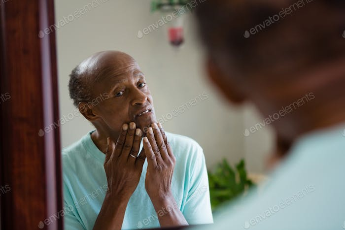 Concerned senior man looking at mirror