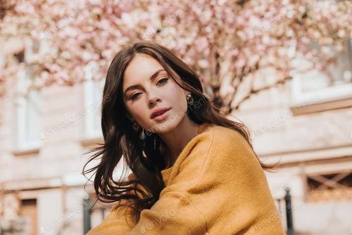 Brunette woman in stylish sweater looks at camera against background of sakura. Lady in yellow outf
