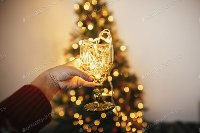 Hand holding stylish vintage glass with garland bulbs inside