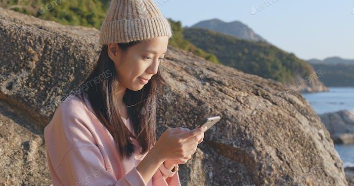 Frau mit Handy mit Seelandschaft Hintergrund