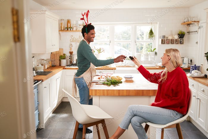 Couple Wearing Fancy Dress Antlers Making A Toast Whilst Preparing Dinner On Christmas Day