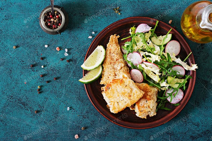Fried white fish fillet and cucumber and radish salad. Top view