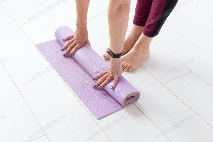 Yoga, peopel concept - Woman rolling her mat after a yoga class