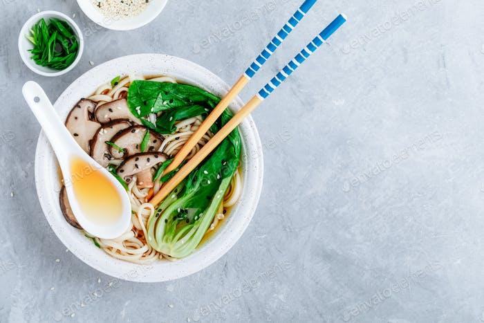 Asian Vegetarian Udon or Ramen noodles soup in bowl with Shiitake mushrooms and Bok Choy