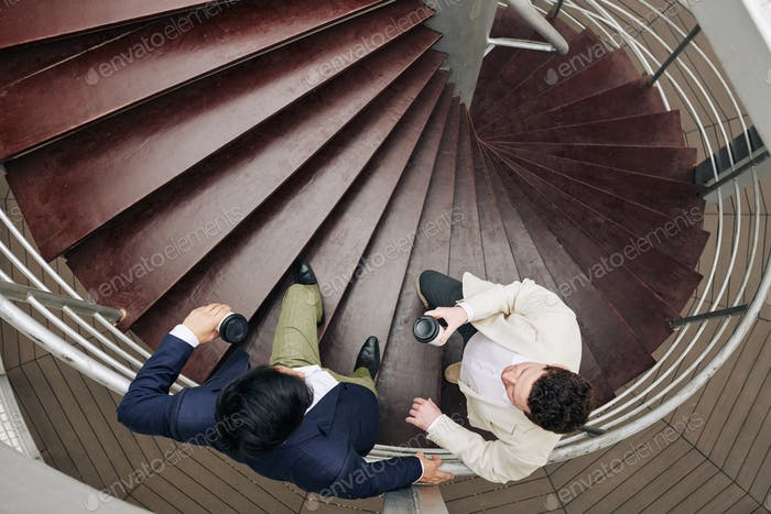 Coworkers talking on spiral staircase