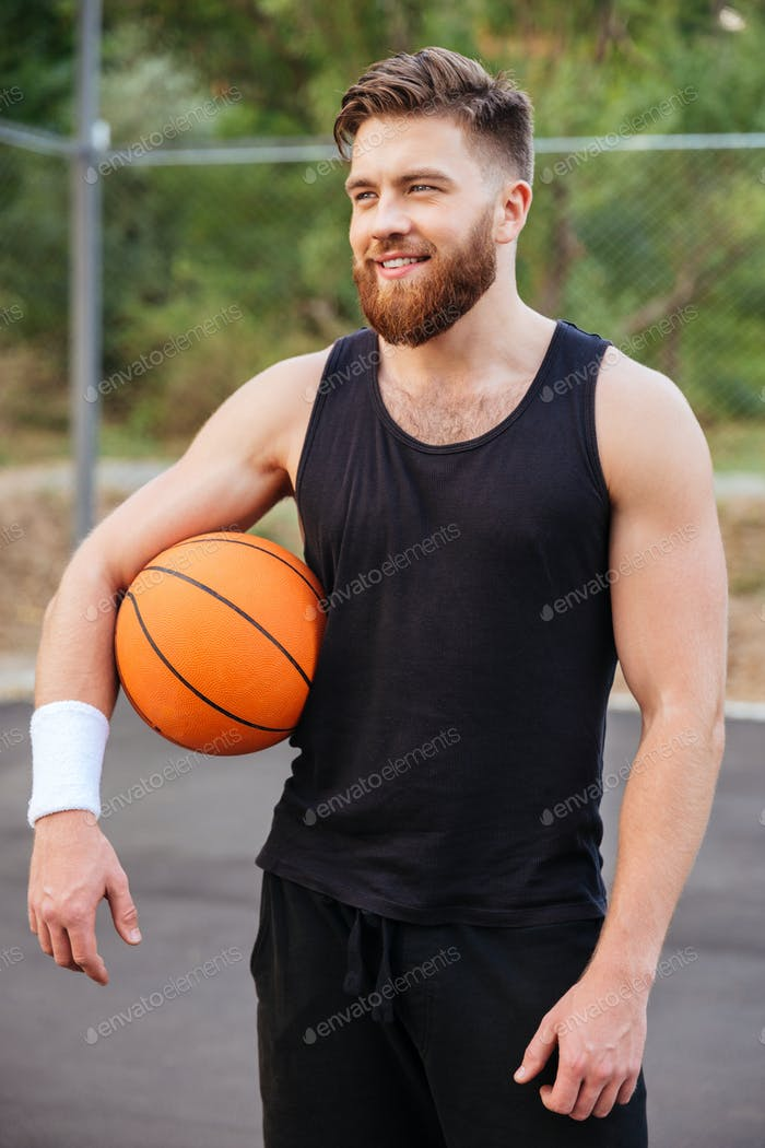 Cheerful happy basketball player standing with ball