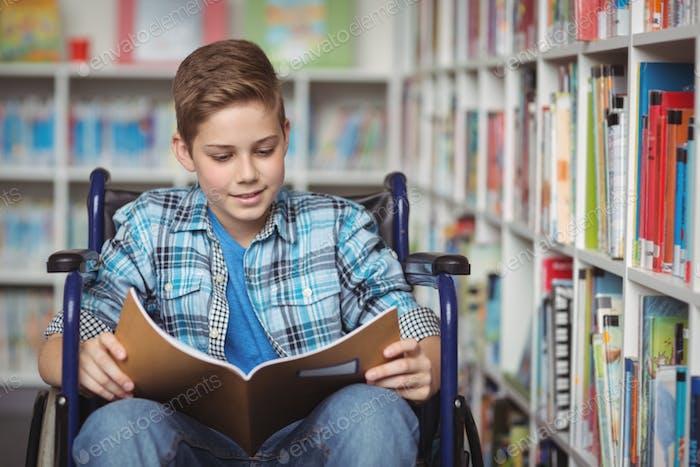 Behinderte Schuljunge lesen Buch in der Bibliothek