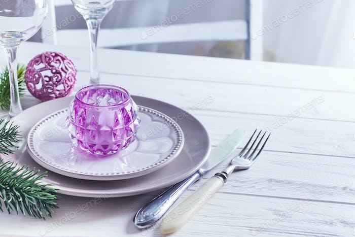 Tischdekoration für Weihnachten weiß Tisch mit lila Dekorelementen mit grünen Ästen