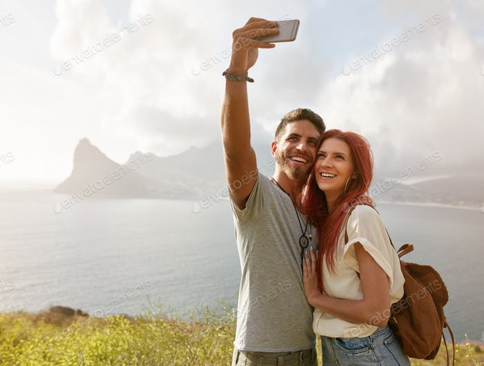 Cheerful young couple on holidays taking selfie