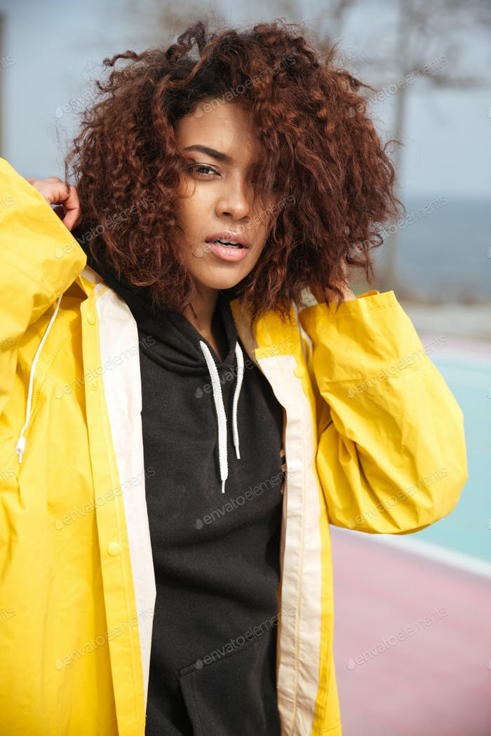 Concentrated african curly young woman wearing yellow coat