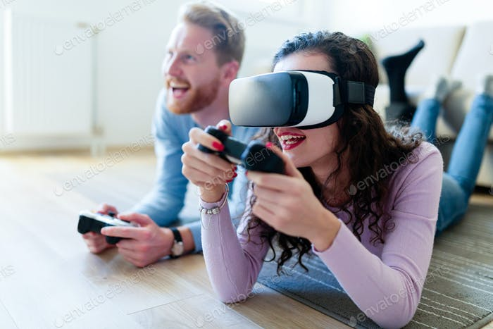 Young couple playing games with virtual reality headset