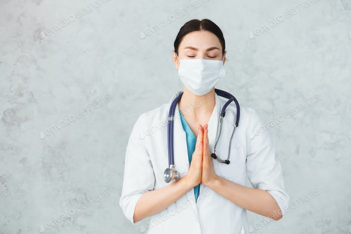 Young female doctor with stethoscope in mask folding hands to praying. Caucasian brunette