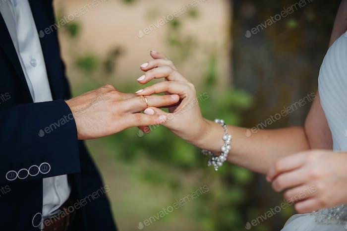 Am Hochzeitstag legt die Braut einen Verlobungsring an den Finger des Bräutigams