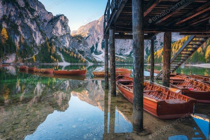 Barcos De madera cerca de la House en el lago Braies al Amanecer en otoño