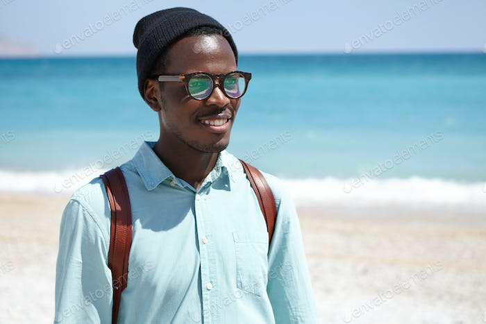 People, travel, holidays and tourism concept. Joyful young dark-skinned male backpacker enjoying pic