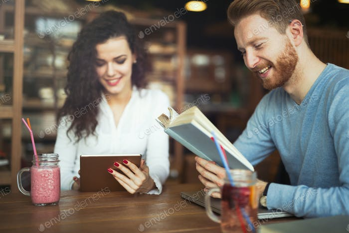 Happy couple studying in library