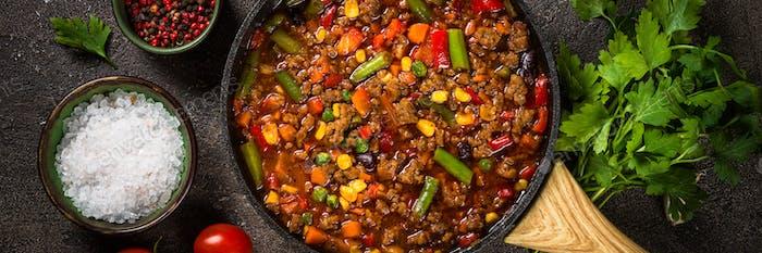Chili con carne in skillet on dark stone table