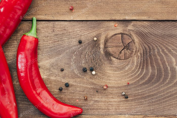 Top view of fresh red hot chili peppers on a wooden table. Copy space.
