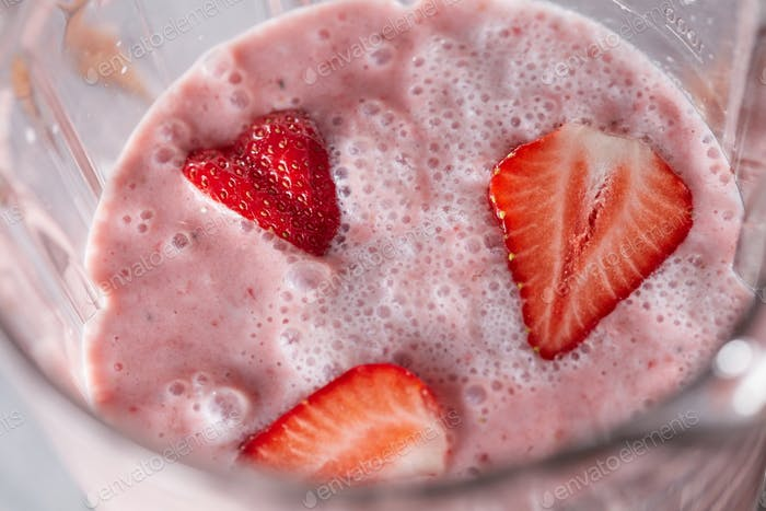 Closeup of a milky-berry shake blender with slices of ripe strawberries. Healthy dessert. Top view