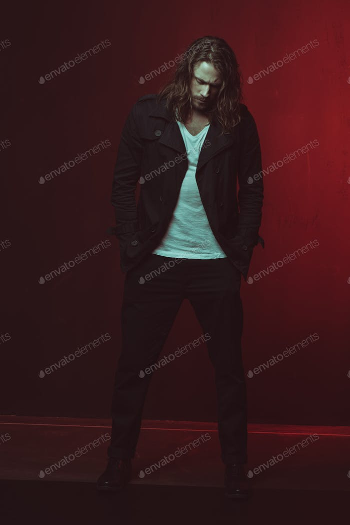 Handsome stylish long haired man posing in studio