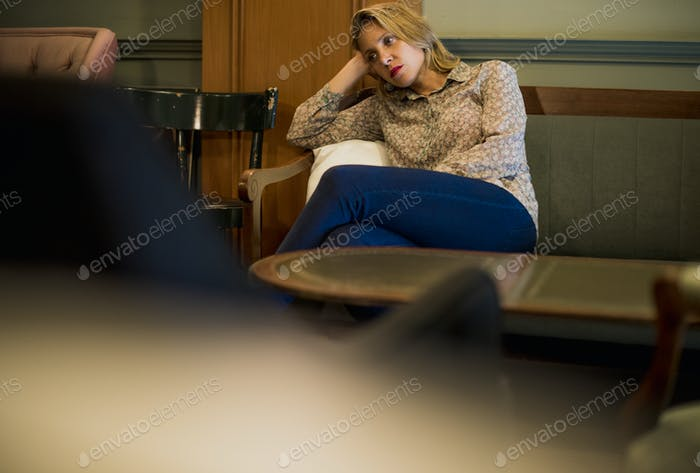 Blond woman waiting at a cafe