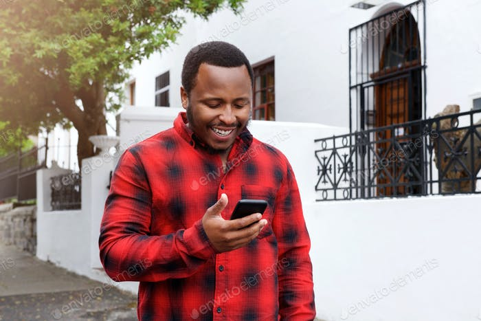 cool black guy smiling outside with cell phone