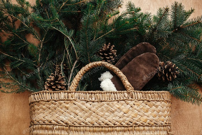 Rustic basket with fir branches, cozy gloves, cones on rustic wooden background