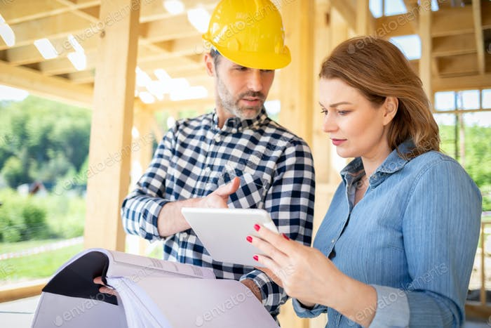 Female homeowner consults blueprints with architect or engineer on construction site