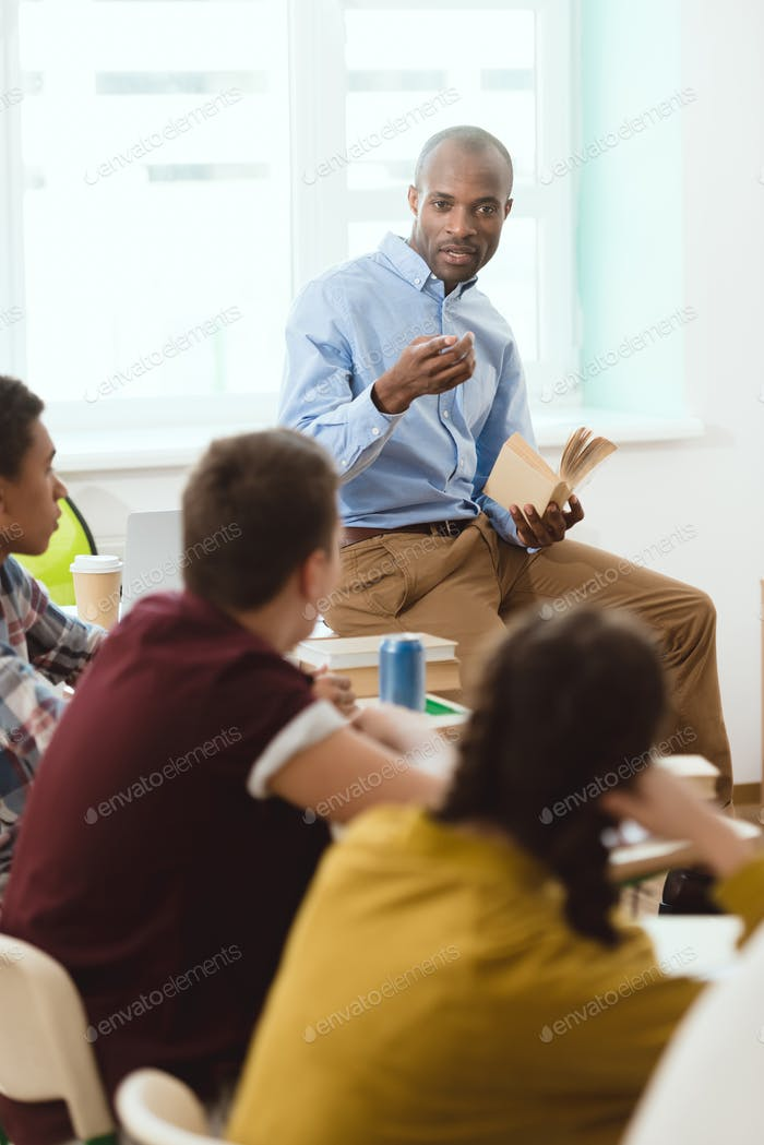 teacher performing lecture for high school students