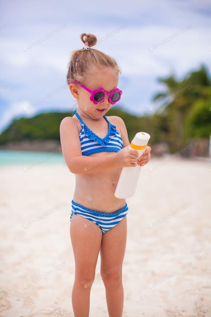 Little cute adorable girl in swimsuit rubs sunscreen herself